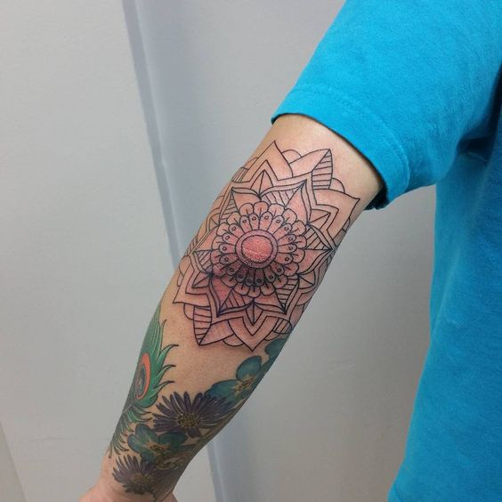 Outline black mandala tattoo on the left elbow