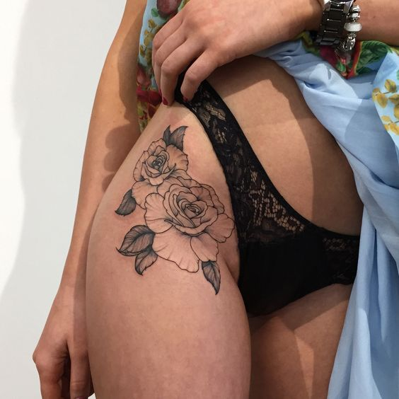 Outline black rose tattoo on the right hip