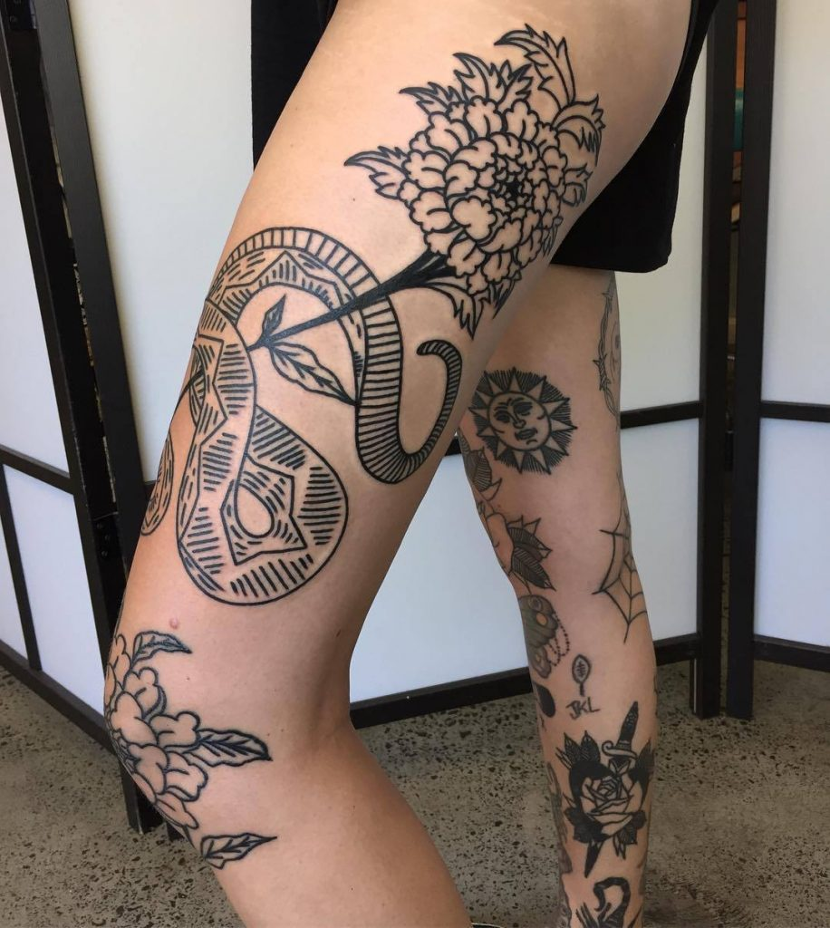 Peony and snake black tattoos on the left thigh