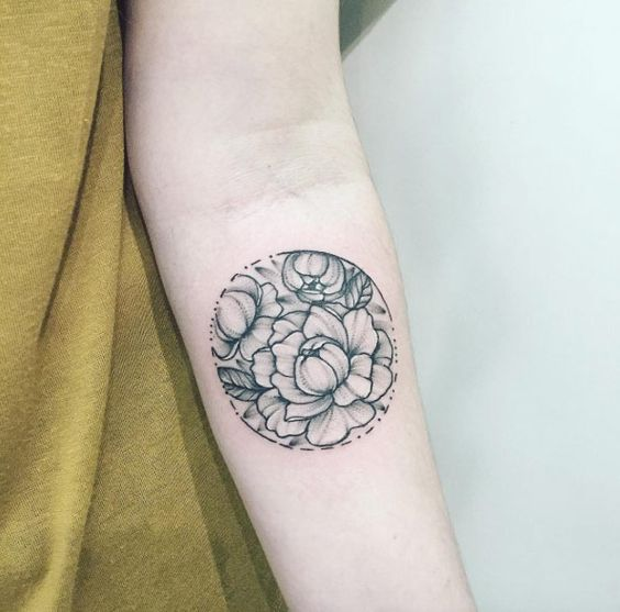 Peony tattoo in a circle on the arm