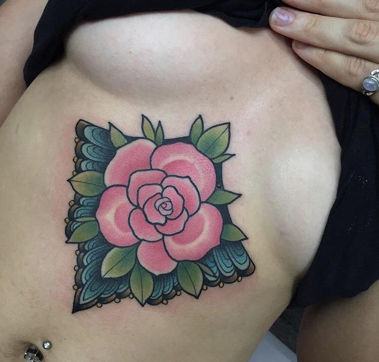 Pink rose breastbone tattoo