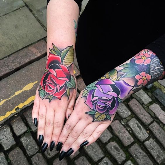 Purple and red traditional style rose tattoos on hands