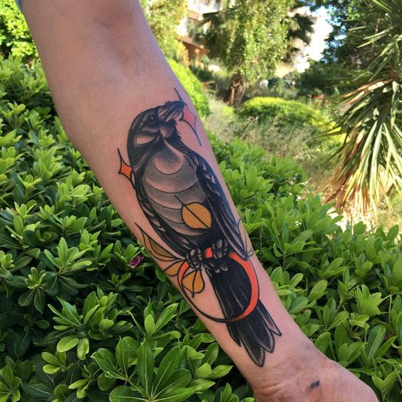 Raven on an orange circle tattoo on the left arm