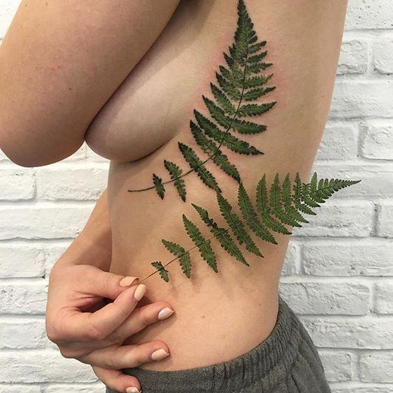 Realistic green fern leaf tattoo on the left rib cage