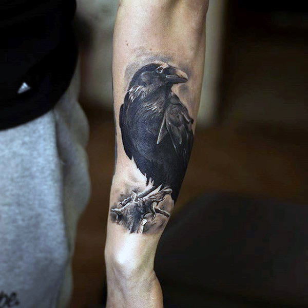 Realistic raven perched on the branch tattoo on the left forearm