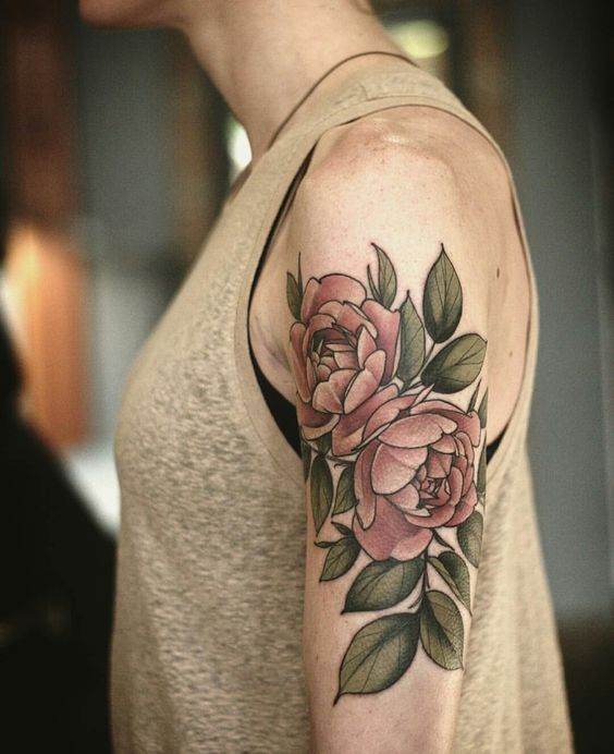 Red peonies with green leaves tattoo on the left arm by alice carrier