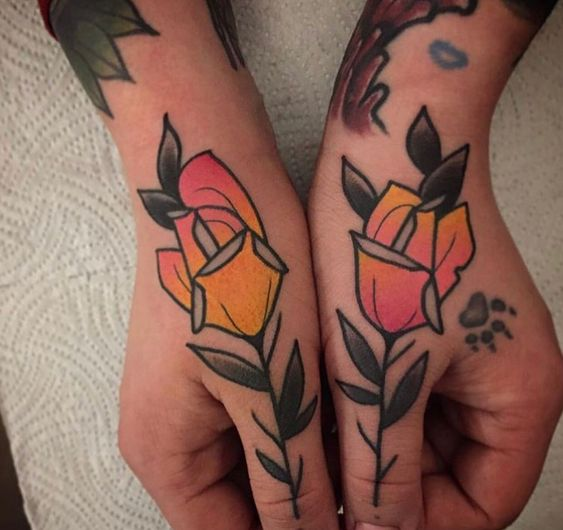Rose tattoos on both thumbs