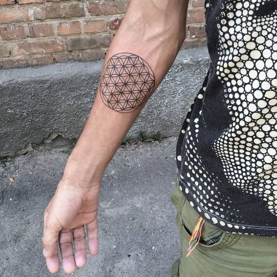 Simple black flower of life tattoo on the right inner arm