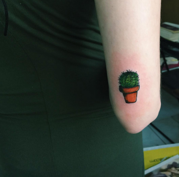 Small cactus tattoo on the right arm above the elbow