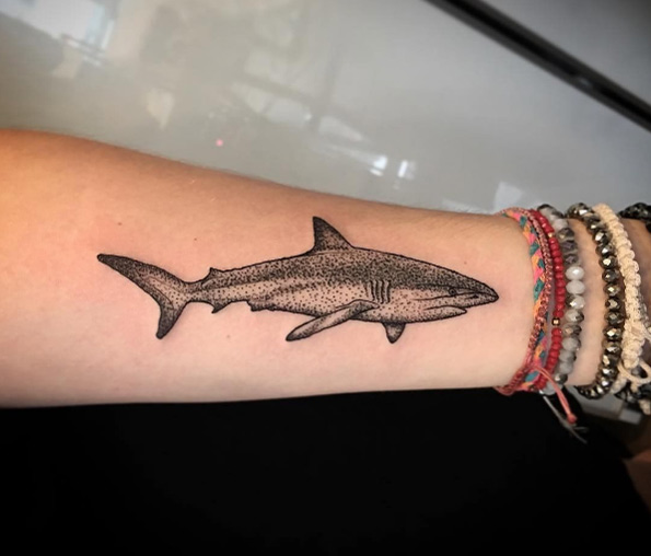 Small dot work style shark tattoo on the left inner arm