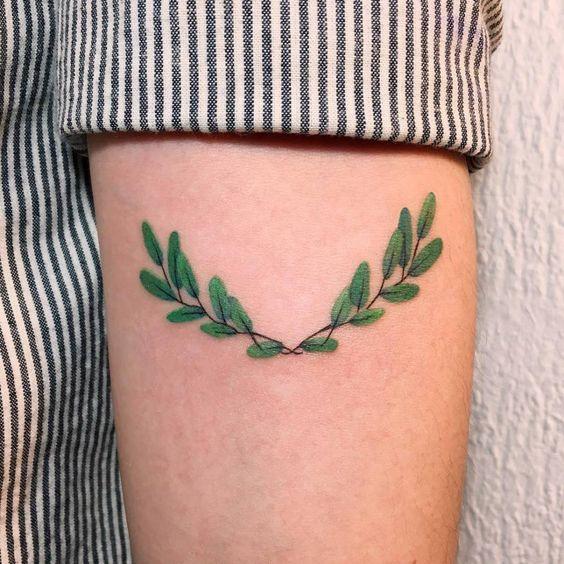 Small laurel wreath tattoo on the left arm