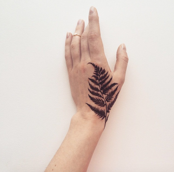 Solid black fern tattoo on the left hand by veronica krasovska