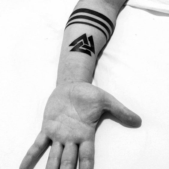 Solid black tattoo of a valknut on the left arm