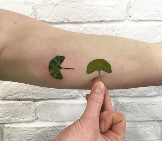 Stuningly realistic green leaf tattoo on the arm