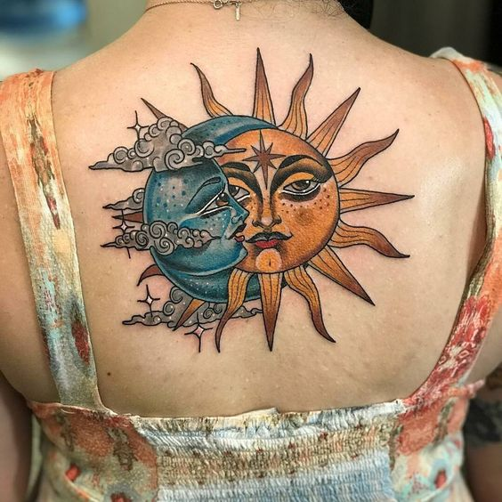 Stylized blue moon and yellow sun tattoo on the upper back