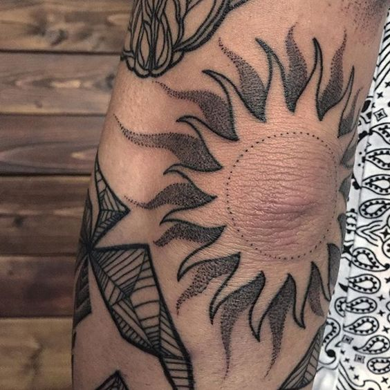 Sun tattoo on the left elbow