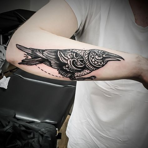 Sylized raven tattoo on the right forearm