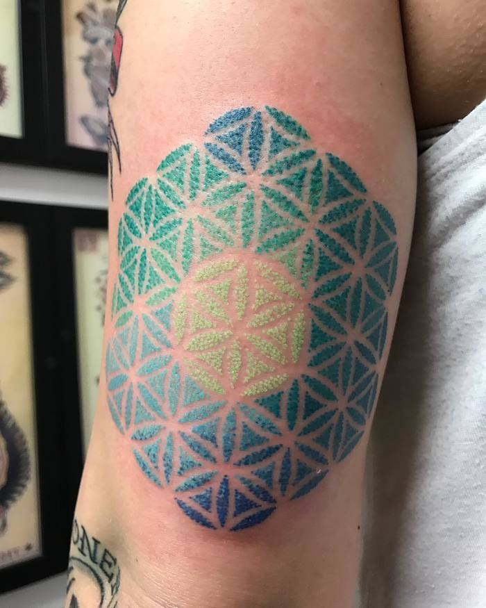 Teal blue and green flower of life tattoo on the left upper arm