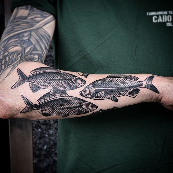 Three black fish tattoo on the left forearm