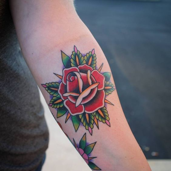 Traditional american rose tattoo on the arm