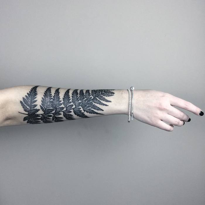Traditional black fern tattoo on the right forearm