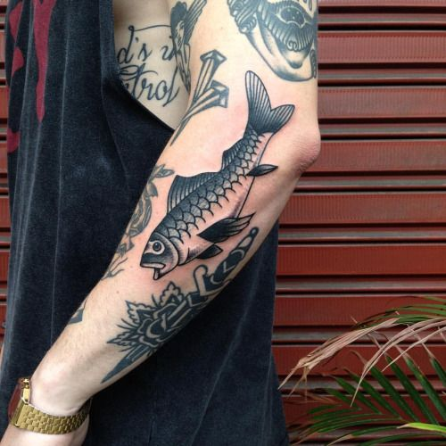 Traditional black tattoo of a fish on the left forearm