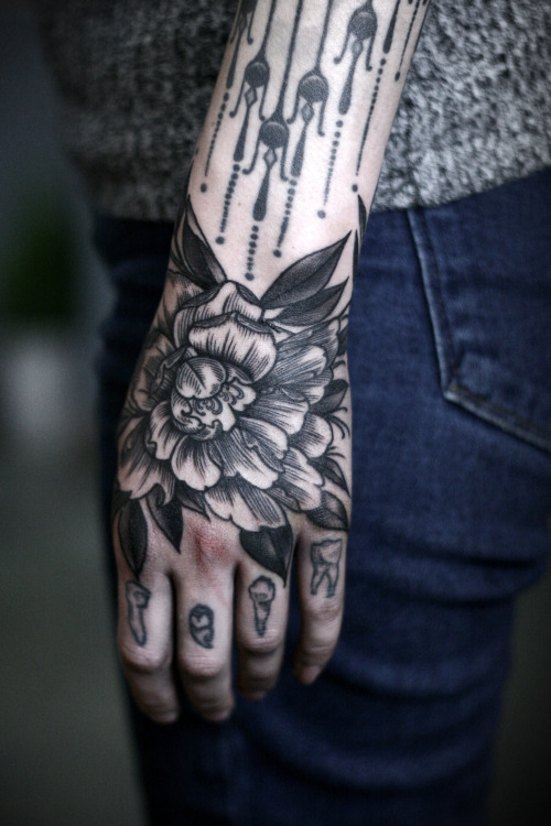 Traditional black tattoo of a peony on the left hand