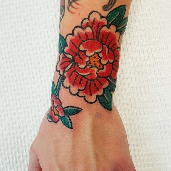 Traditional tattoo of a red peony on the left hand