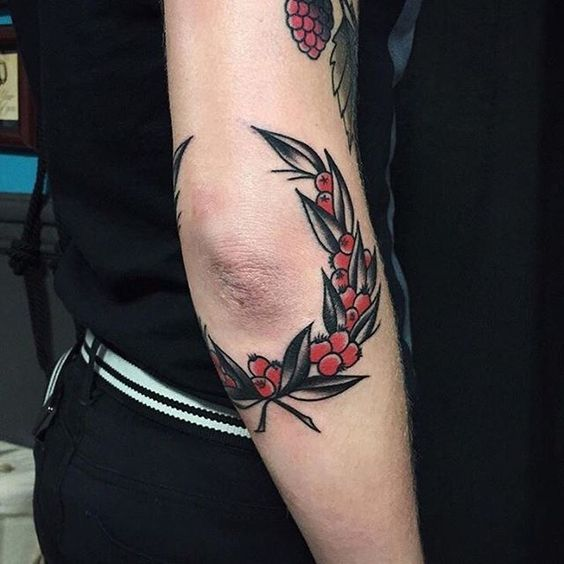 Traditional wildflower wreath tattoo on the elbow