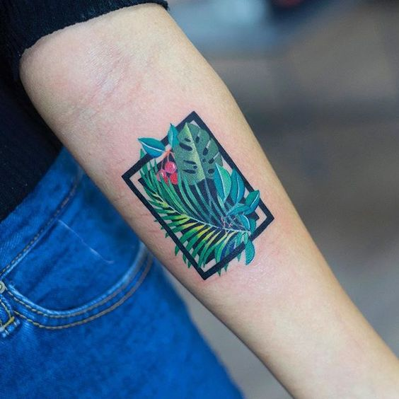 Tropical leaves in a rectangle tattoo on the arm