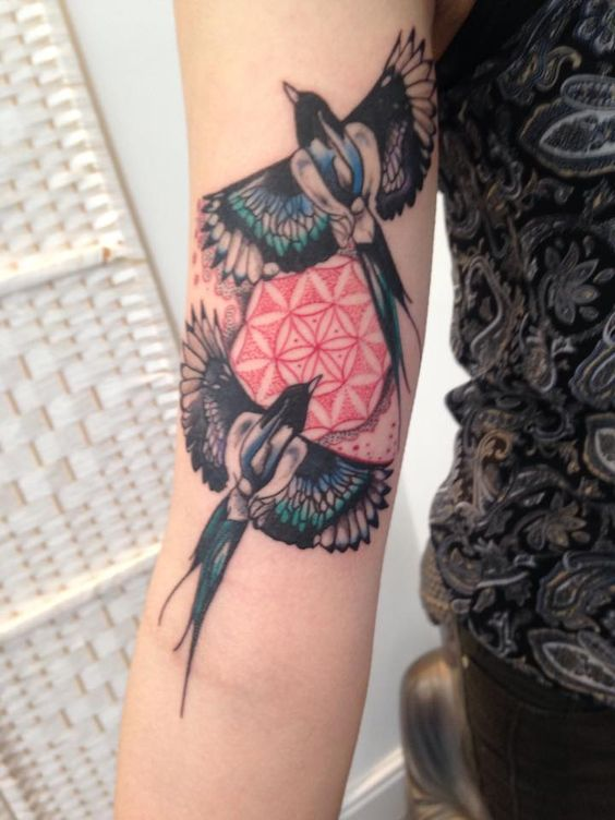 Two magpies representing joy and sorrow and a flower of life tattoo on the right arm