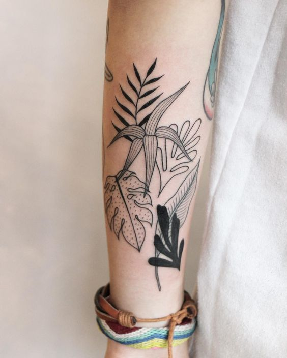 Various tropical leaves tattoo on the forearm