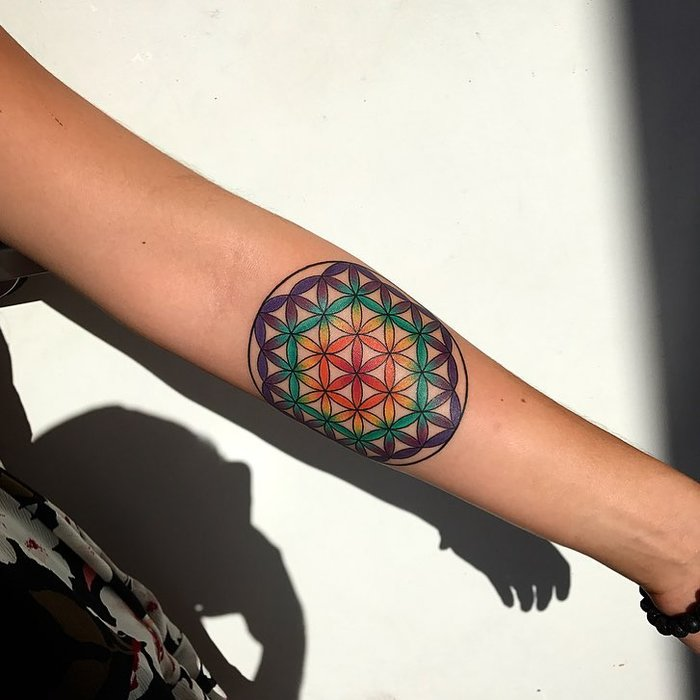 Watercolor flower of life tattoo on the left inner arm