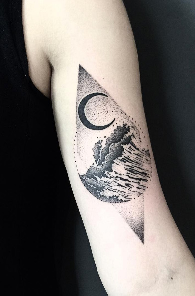 Waves and crescent moon tattoo on the right upper arm