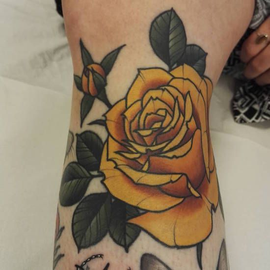 Yellow traditional rose tattoo on the arm