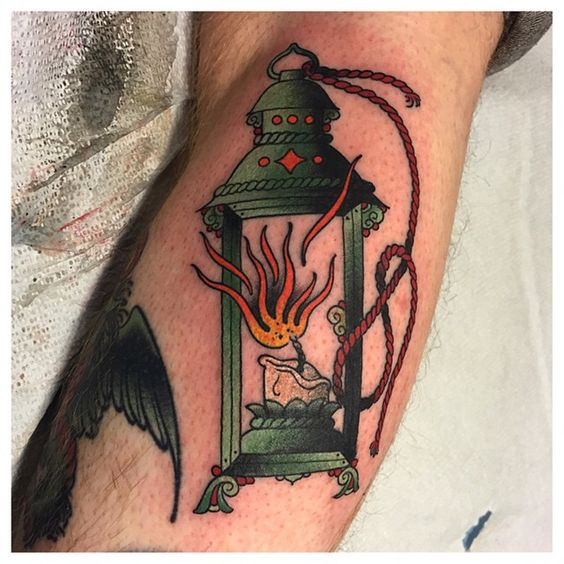 Beautiful green lantern with a burning candle tattoo