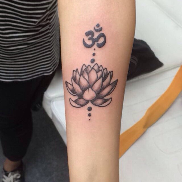 Black and grey lotus flower and om tattoo on the forearm