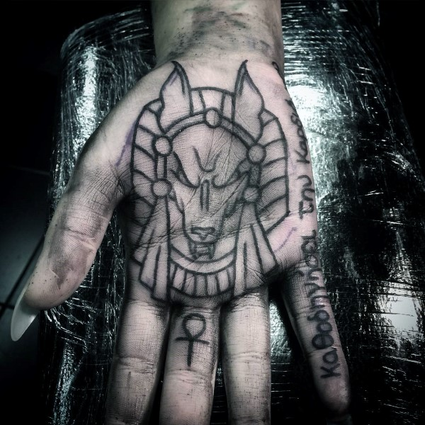 Black anubis tattoo and ankh symbol on the palm