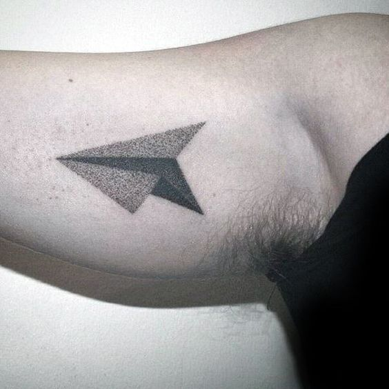 Black dot work paper plane on the bicep
