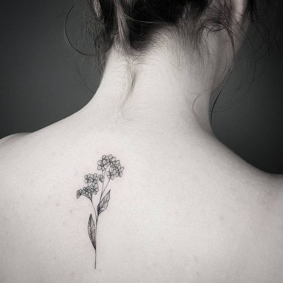 Black forget me not tattoo on the back