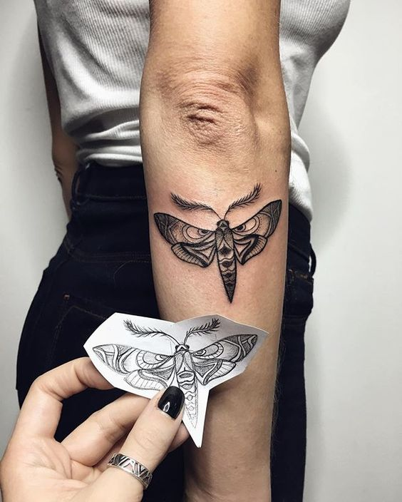 Black moth tattoo on the right forearm