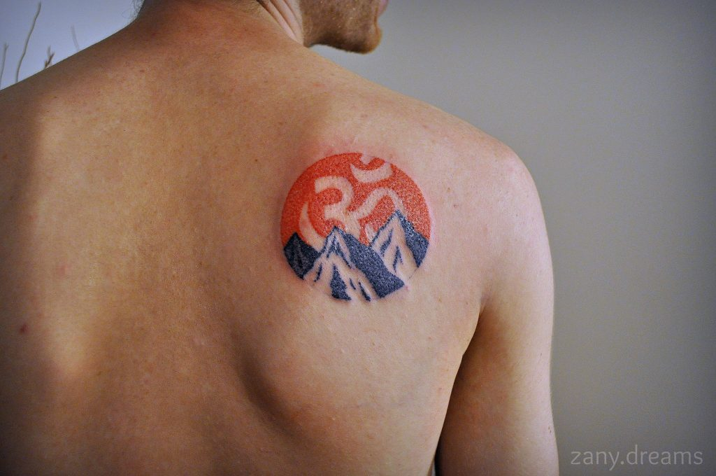 Circular om and mountains tattoo on the right shoulder blade