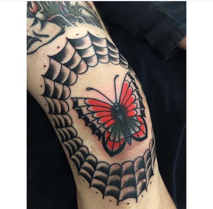 Classic butterfly and spider web tattoo on the left knee