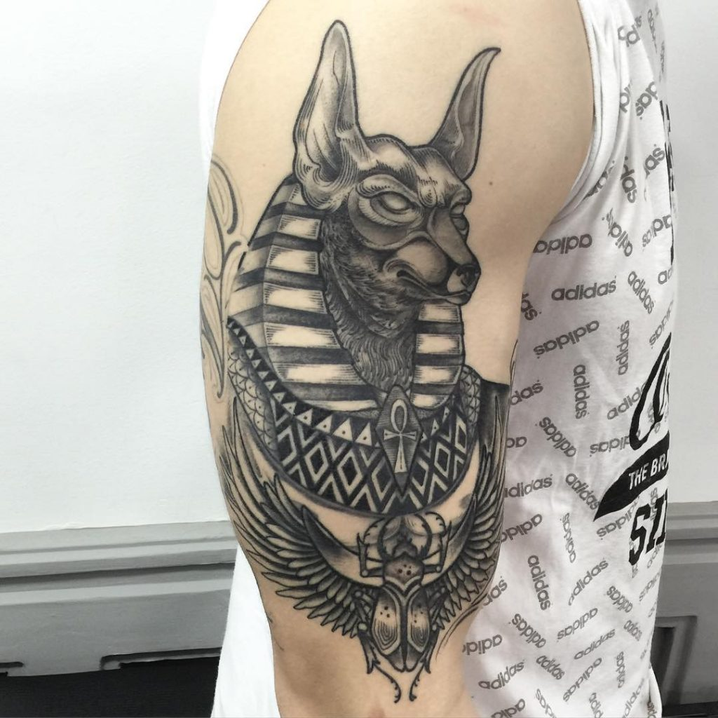 Detailed anubis tattoo on the right arm