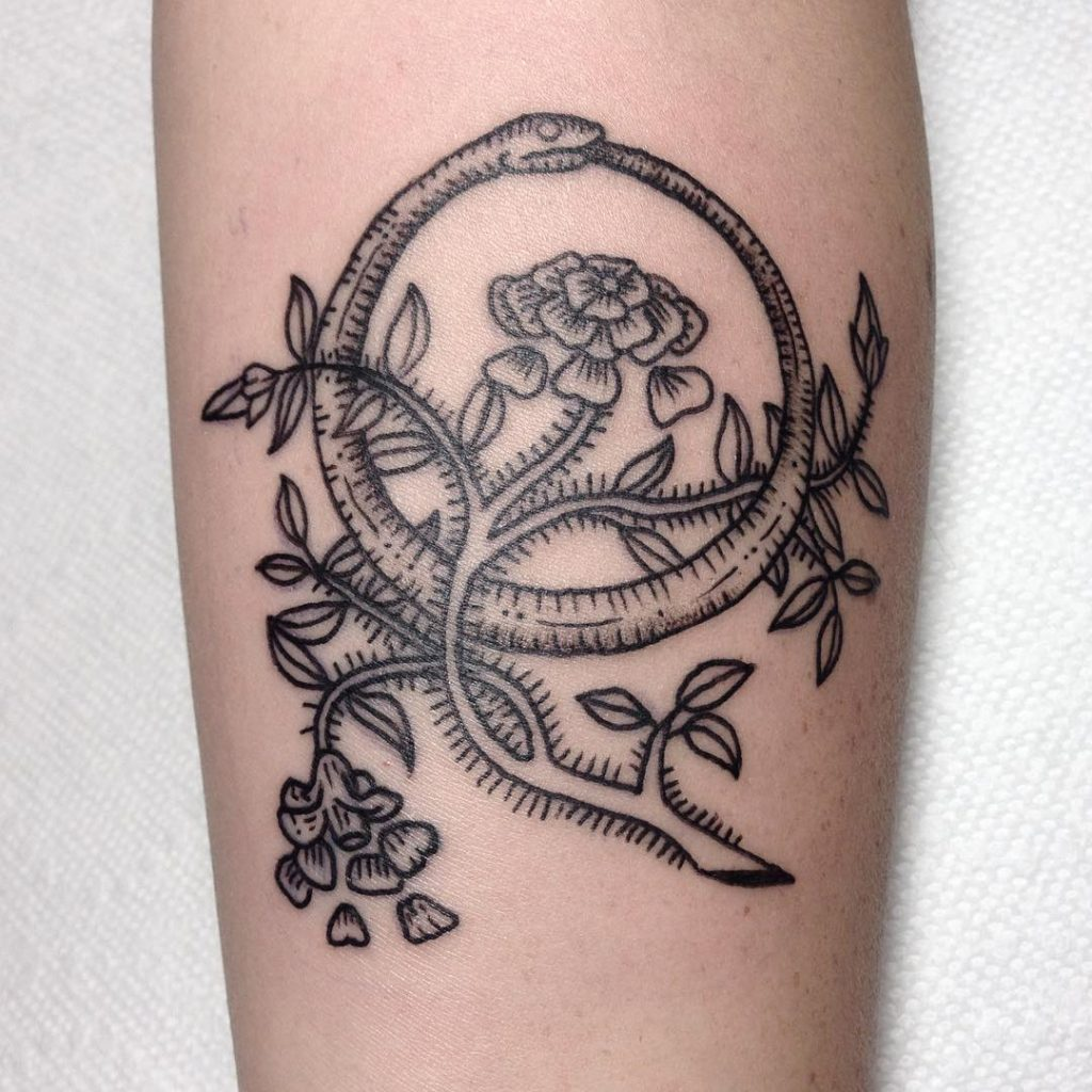 Flower branch and ouroboros tattoo
