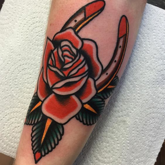 Horseshoe with red rose tattoo on the arm