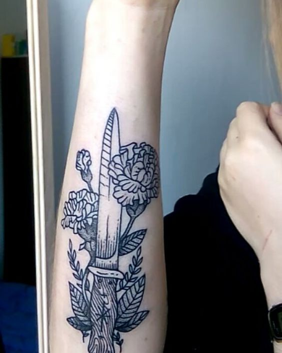 Knife and peony tattoo on the forearm
