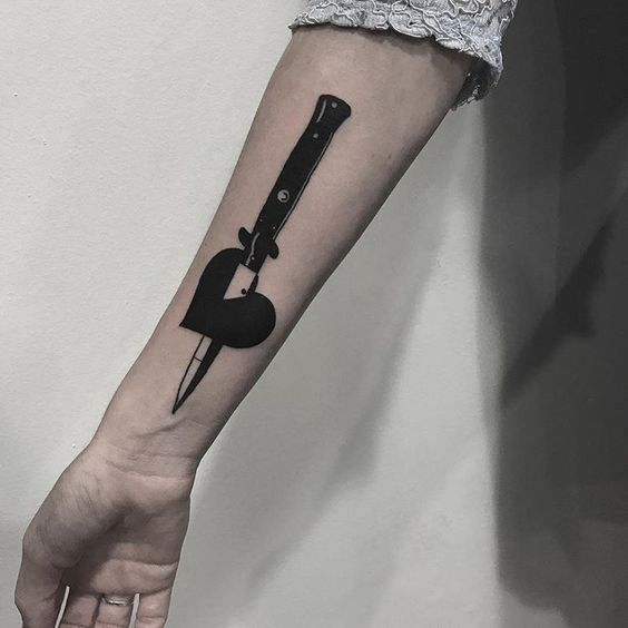 Knife pierced black heart tattoo