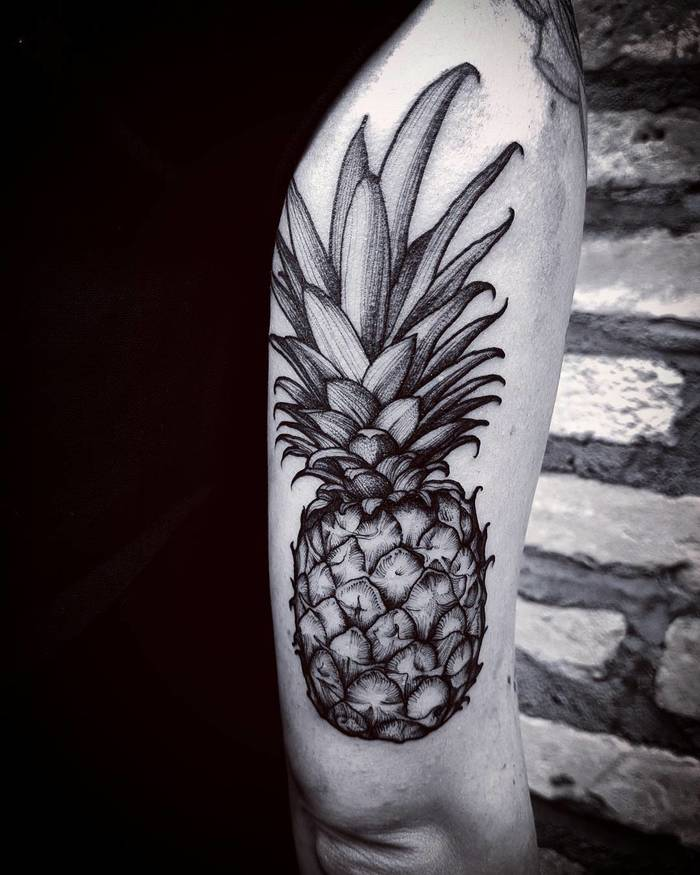 Large hyper realistic pineapple tattoo on the back of the right arm