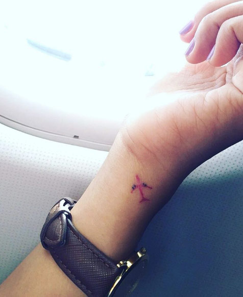 Little red plane tattoo on the left wrist